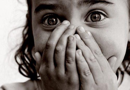 Bambina spaventata con le mani sulla bocca